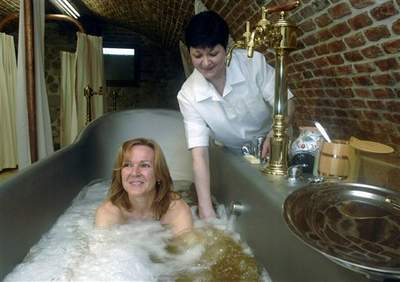Jana Tymlova, left, enjoys a soak in the Real Beer Baths launched by the family brewery Chodovar in Chodova Plana, Czech Republic, Thursday, March 23, 2006.